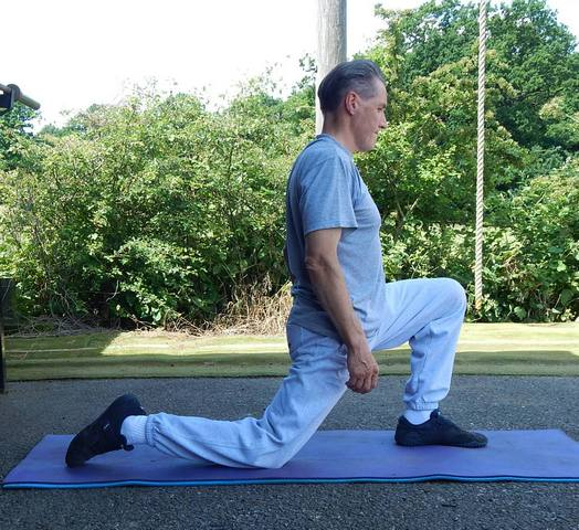 Kettlebell Instructor Performing Hip Flexor Stretching Exercises for Kettlebell Training Preparation. Start Position
