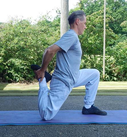 A Kettlebell Instructor demonstrating a Full Static hip Flexor Stretch for Kettlebell Training Preparation