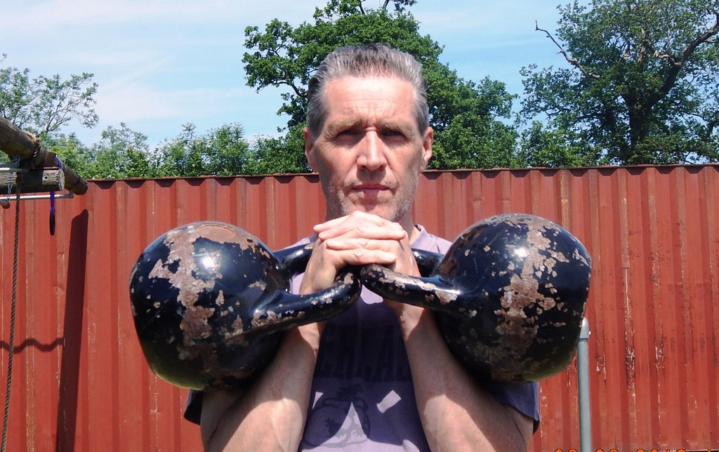 A Double Kettlebell Clean demonstrated by Personal Fitness Trainer at Outdoor Gym
