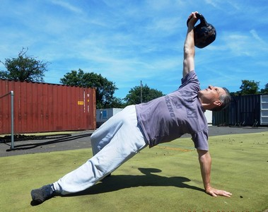 Fitness coach performing a Turkish Getup kettlebell workout