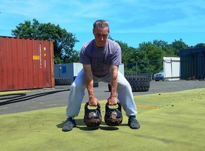 Fitness-Coach-Kettlebell-Lifting-and-performing-with-Double-Kettlerbells
