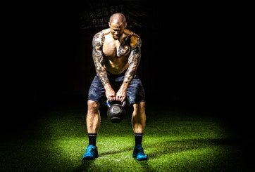 Tattooed Fitness Trainer Kettlebell Lifting