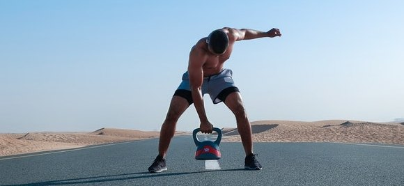 Man-doing-kettlebell-Training-and-a-kettlebell-workout-exercise-routine-on-a-deserted-highway