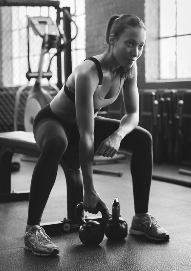 Kettlebell Training Preparation with Woman Kettlebell Instructor Sat on Bench in Gym