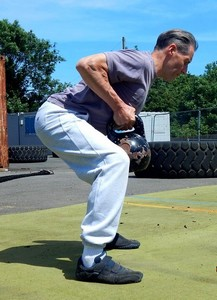 Fitness Coach executing a Double Row kettlebell workout in the Finish Position