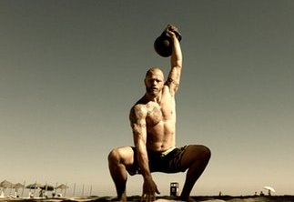 Kettlebell Workouts held on a Beach with a Man Performing a Single Arm Over Head Squat